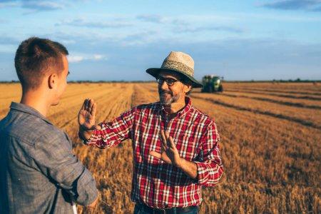 two ranchers talking outdoor on wheat field