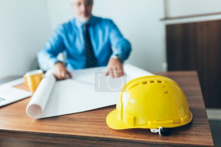 Photo for Close up of yellow helmet on desk and engineer in blurred background - Royalty Free Image