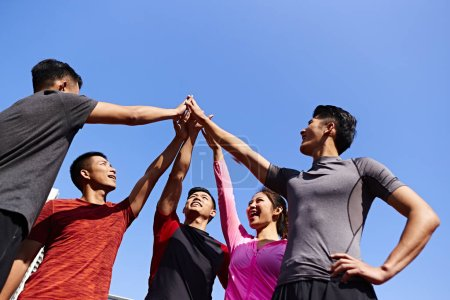 team of asian young adult sportsmen and sportswoman putting hands together to show unity and teamwork spirit.