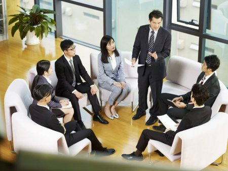 Boss speaking to team of asian business people sit...