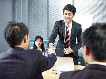Photo pour Deux hommes d'affaires asiatiques serrant la main sur la table de réunion avant la négociation . - image libre de droit