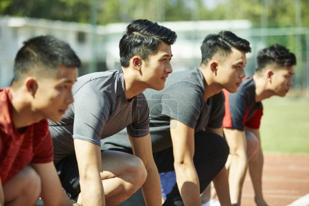 Photo for Young asian track and field athletes sprinters setting on starting line. - Royalty Free Image