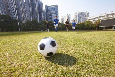 Foto de Jóvenes asiáticos fútbol futbolistas persiguiendo la bola durante un partido - Imagen libre de derechos