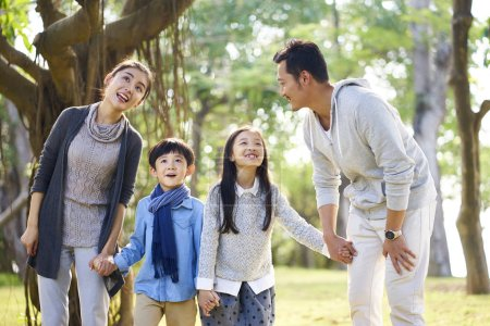 Photo for Asian family with two children having fun exploring woods in a park. - Royalty Free Image