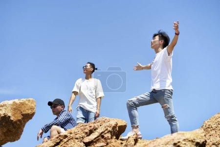 Photo pour Groupe de jeunes asiatiques adultes hommes debout sur le dessus de rochers contre ciel bleu profiter du soleil et l'air frais - image libre de droit
