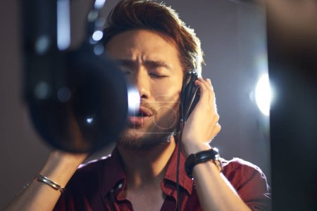Photo for Young asian adult man enjoying singing a song in modern recording studio - Royalty Free Image