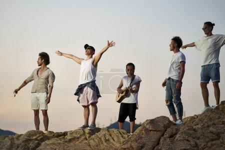 Photo pour Membres d'un groupe de rock debout sur des rochers au bord de la mer chantant de la guitare - image libre de droit