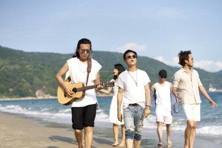 Photo pour Membres d'un groupe de rock marchant sur la plage jouant de la guitare - image libre de droit
