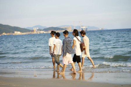 Photo pour Groupe de cinq jeunes hommes asiatiques marchant dans l'eau de mer sur la plage - image libre de droit