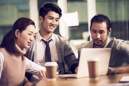 Photo pour Équipe de trois jeunes entrepreneurs asiatiques se réunissant au bureau ayant une discussion à l'aide d'un ordinateur portable au bureau - image libre de droit