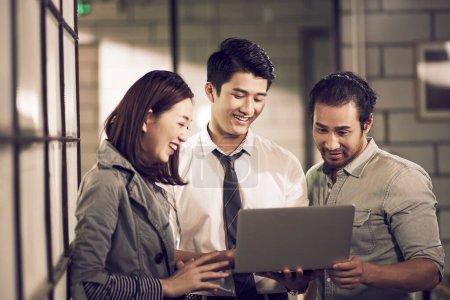 Photo pour Une équipe de trois jeunes entrepreneurs asiatiques regardant ordinateur portable ensemble dans le bureau - image libre de droit