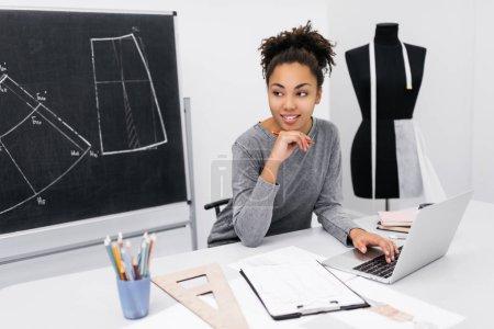 Photo pour Portrait de jeune designer afro-américain souriant projet de planification, dactylographier sur le clavier, assis sur le lieu de travail. Étudiant à l'université utilisant un ordinateur portable pour le travail, l'apprentissage de l'illustration de mode dans un atelier moderne . - image libre de droit