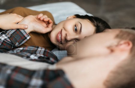 Photo pour Young lovely couple together in cozy apartments looking and caring each other. Attractive woman with beautiful face and smile lying on comfortable bad with adorable man. Successful life concept. - image libre de droit