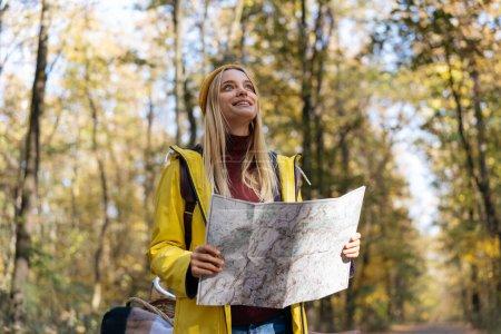 Photo pour Belle femme hipster utilisant la carte pour naviguer dans la forêt d'automne. Touriste heureux essayant de trouver le meilleur moyen. Style de vie actif, concept de voyage - image libre de droit