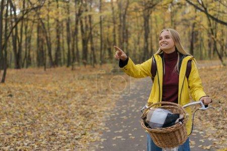 Photo pour Portrait d'une belle femme souriante chevauchant un vélo dans le parc, montrant doigt sur l'espace de copie. Concept d'automne - image libre de droit