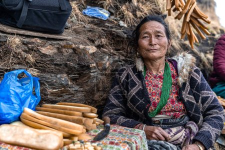 A middle-aged Asian woman selling Himalayan gold d...