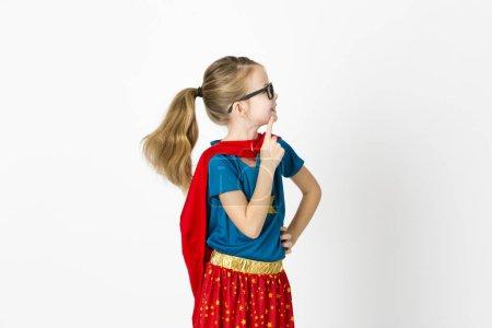Photo pour Blonde supergirl avec des lunettes et robe rouge et chemise bleue pose dans le studio - image libre de droit