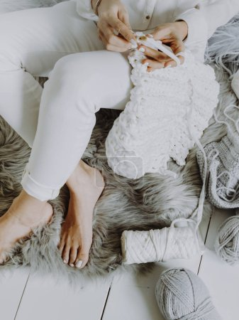 Photo for Woman sitting on wooden floor and crocheting with white wool - Royalty Free Image