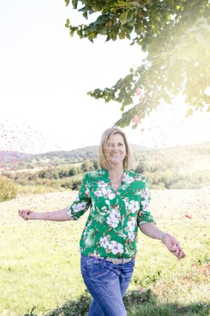 Photo for Happy satisfied woman throwing confetti in meadow at summer sunny day - Royalty Free Image
