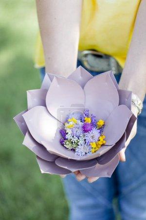 Photo pour Female hands holding beautiful purple floral bowl with flowers at meadow - image libre de droit