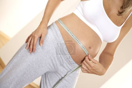 woman measuring abdominal circumference by tape, close-up
