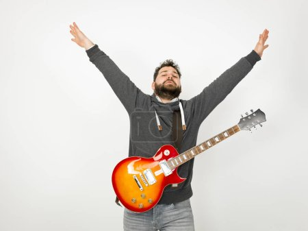 cool man with black hair and beard wearing grey hoodie playing electric guitar in front of white background