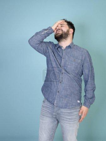 Photo pour Homme frais et jeune avec le cheveu noir et la barbe noire grimaçant tout en posant devant le fond bleu de mur - image libre de droit