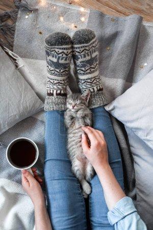 Photo pour Une fille en chaussettes tricotées s'assoit sur une couverture, tient sa main une tasse de café et un chaton - image libre de droit