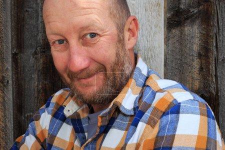 Photo pour Homme posant avec un fond en bois naturel . - image libre de droit