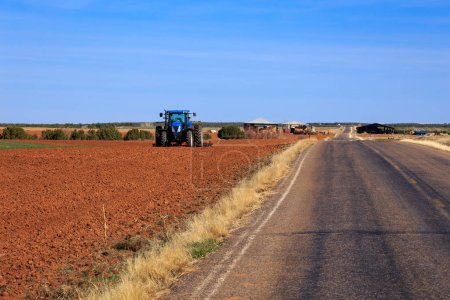 Photo for Tractor turning up the soil, rural landscape - Royalty Free Image
