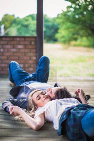Foto de La joven pareja adorable de amor mentira cara a cara al aire libre y sonriente - Imagen libre de derechos