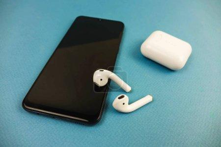 berlin deutschland 03.11.2019. Apple-Kopfhörer liegen auf einem schwarzen Telefon.
