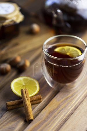 Tea in glass teacup with lemon. Near glass teapot, cinnamon sticks, jam in jar, hazelnuts and lemon at wood background