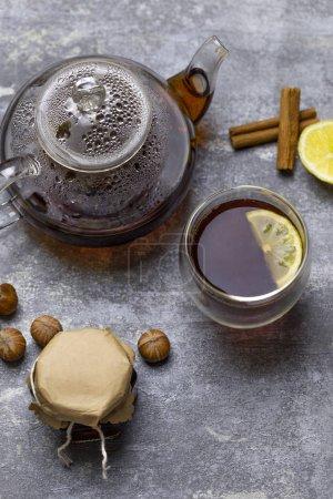 Tea in glass teacup with lemon. Near glass teapot, cinnamon sticks, jam in jar, hazelnuts and lemon at gray background