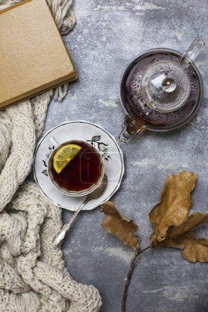 Cup with black tea and lemon and saucer, spoon, glass teapot, book, oak leaves and knitted scarf near, at gray background
