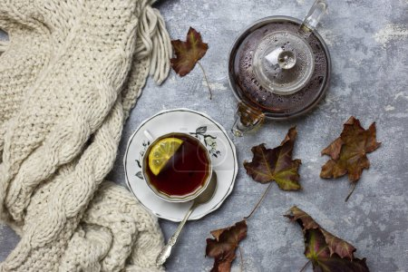 Cup with black tea and lemon and saucer, maple leaves and knitted scarf near, an gray background
