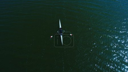 Aerial view of athlete rowing on a canoe