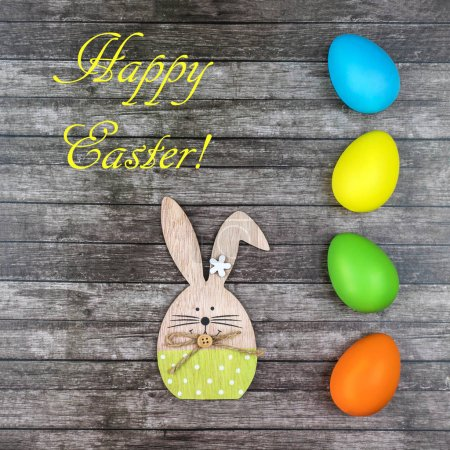 Photo for Colored Easter eggs and bunny at wooden table with text Happy Easter. - Royalty Free Image