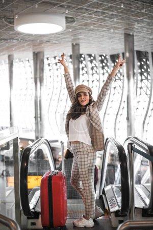 Beautiful business woman on escalator in airport.