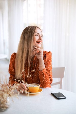 Photo for Beautiful young smiling woman drinking coffee at cafe. - Royalty Free Image