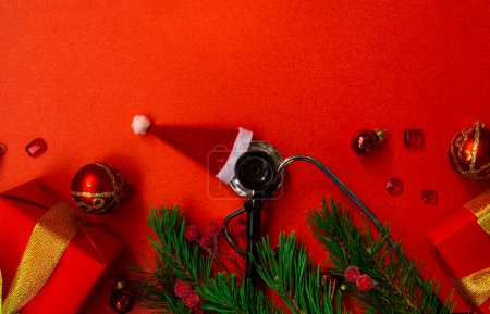 Photo pour Medical Christmas banner with pills, stethoscope, test tubes, gift box, Santa hat, Christmas toys, heart, and a Christmas tree on a red background. Copyspace. The new year's cure is categorical. Christmas medical flatly. - image libre de droit