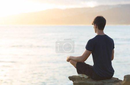 Photo pour Un jeune homme regardant le coucher de soleil de l'océan tout en faisant une pose de yoga de méditation. Relaxation et réflexion . - image libre de droit