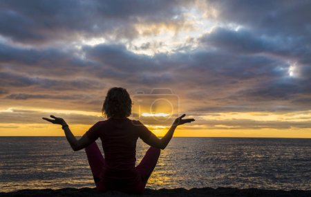 Woman sits as yogi with outstretched hands and con...