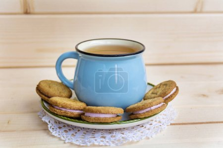 Photo for Blue mug of tea and sandwich cookies on wooden background - Royalty Free Image