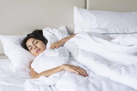 Foto de Mujer joven durmiendo en cama blanca - Imagen libre de derechos