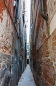 Venice, Italy - June 16, 2014: Super narrow street architecture in old town Venice, Italy