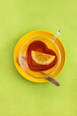 Tasse schwarzer Tee herzförmige Tasse und gelbe Untertasse, Draufsicht auf gr