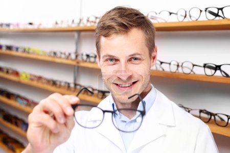 Oculist.The man chooses spectacle frames in the optical salon