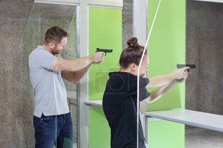 Shooting with a gun. A woman and a man at the shooting range