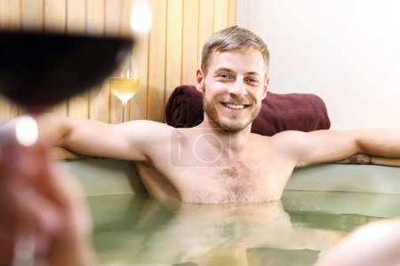 Photo pour Bain jacuzzi.Un jeune homme détendu et souriant qui se relaxe dans une baignoire avec de l'eau . - image libre de droit